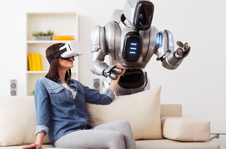 woman with VR headset holding hands with a robot