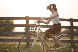 what is augmented reality. Girl riding her bike while wearing a VR headset
