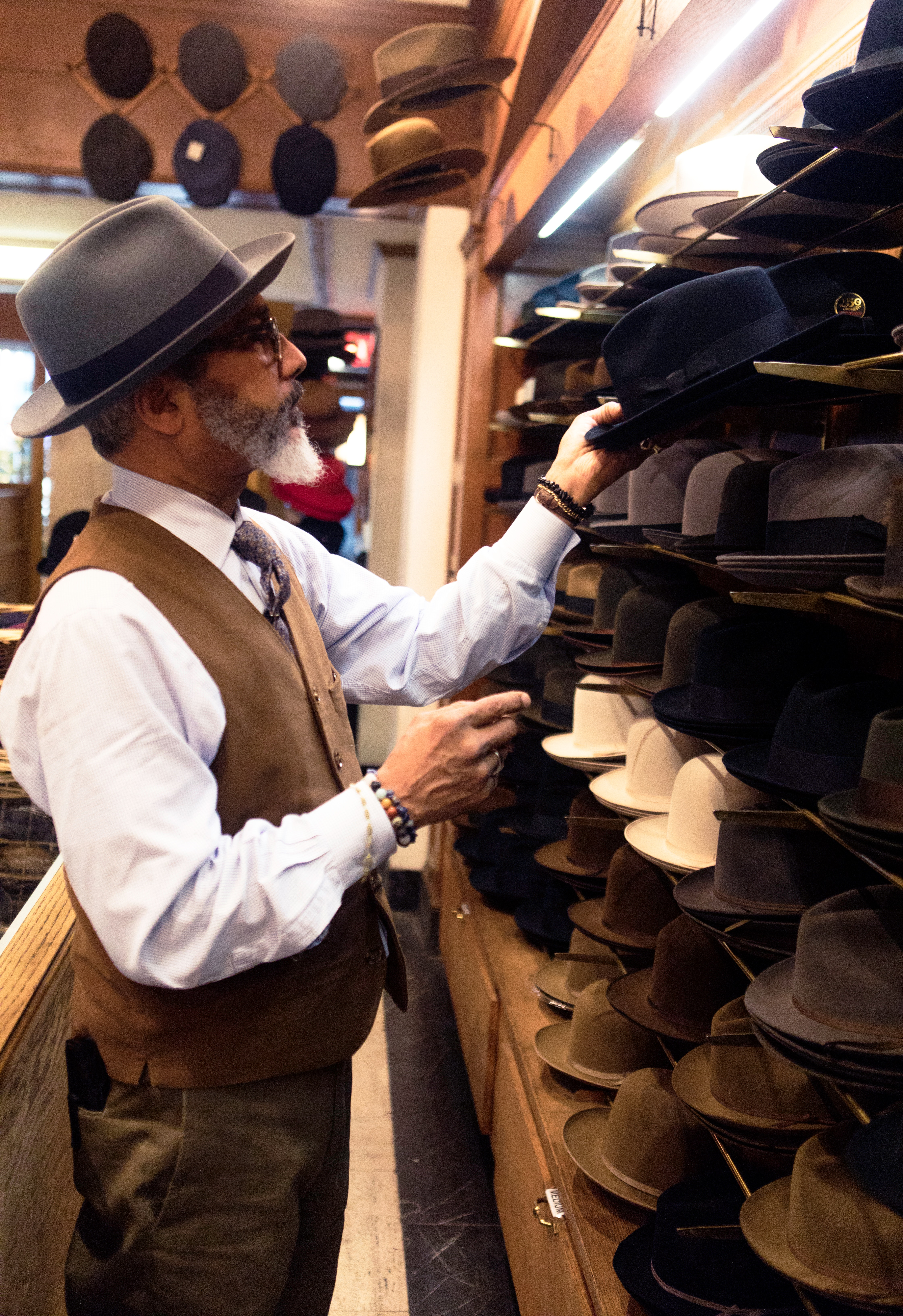 Image of a vintage man picking out hats