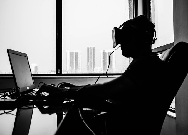 silhouette of a man using oculus while typing on laptop